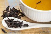Se Chung Oolong tea - um copo branco de bebida e solta folhas de colher de chá