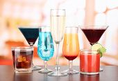 stock photo of bloody mary  - Several glasses of different drinks on bright background - JPG