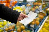 Hand, holding a shopping list with day to day groceries in front of crates with fresh, colorful frui
