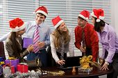 stock photo of office party  - Portrait of friendly business team wearing Santa caps while communicating in office - JPG