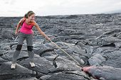 Hawaii Big Island lava tourist on volcano poking stick in red hot moving lava. flowing lava from Kil