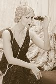 Old photo with reenacted scene of a classy lady in roaring twenties style using a pair of opera glas