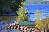 stock photo of moosehead  - Green hull canoe beached on stony shore of Moosehead Lake - JPG