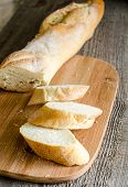 stock photo of baguette  - Sliced French Bread Baguette on the cutting board - JPG