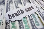stock photo of cash  - Closeup of health care newspaper headline on cash - JPG
