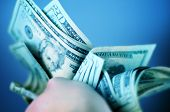 stock photo of twenty dollars  - Hard Earned Dollars - Twenty American Dollar Bills. Cash in Hand. Bluish Color Theme.