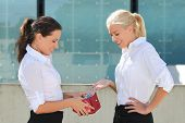 Business Woman Taking Euro Banknotes Out From Wallet And Giving Them To Other Woman
