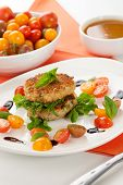 stock photo of crab-cakes  - Close up of crab cakes and cherry tomato salad appetizer garnished with basil and balsamic vinegar sauce - JPG