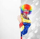 stock photo of joker  - Smiling clown holding a blank sign - JPG