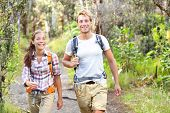Outdoor activity couple hiking - happy hikers walking in forest. Hiker couple laughing and smiling.