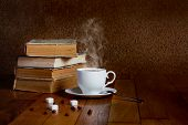 image of poetry  - Hot cup of fresh coffee on the wooden table and a stack of books to read - JPG