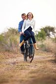 Happy Couple Riding Old Bicylce On Dirt Road
