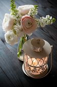 stock photo of buttercup  - Home festive wedding decor exquisite bouquet of flowers buttercups and white lilacs and lantern candle on a dark wooden board - JPG