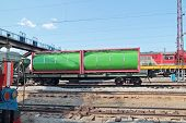 Green Cistern Of Freight Train At Railway Station With Many Electric Wires At Summer