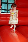 foto of bounce house  - Little beautiful happy girl jumps on red bouncy castle and laughs