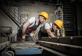 stock photo of heavy equipment operator  - Worker and foreman in a safety hats performing quality check on a factory   - JPG