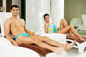 Young cheerful couple relaxing with refreshing drinks near swimming pool