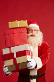 Santa Claus with pile of giftboxes looking at camera