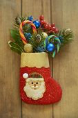 Christmas stocking with fir branches, berries and candy canes