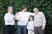Four Generations Of Men And A Baby Girl In A Park