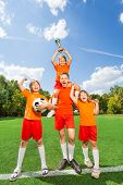 stock photo of pyramid shape  - Excited children with won cup stand in pyramid shape together on grass - JPG