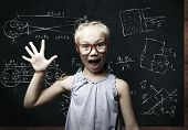 Genius girl in red glasses near blackboard with formulas