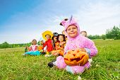 Many Halloween kids wear costumes sit in long row
