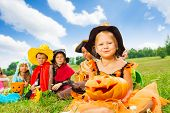 Many kids in Halloween costumes sitting close