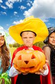 Boy in Halloween costume with hat makes face