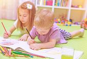 Happy baby boy & girl enjoying homework, preschool developing drawing skills, talented children lear