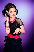 Funny cheerful girl listens to music on headphones. Childhood.