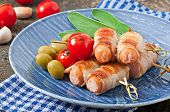 Grilled sausages wrapped in strips of bacon with tomatoes and sage leaves