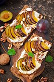Vegetarian Diet sandwiches Crispbread with cottage cheese, plums, nuts and honey on old wooden backg