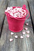 Beads in metal bucket on wooden background