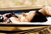 Young woman lying in hammock.
