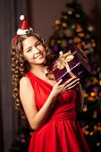 Beautiful young smiling santa girl. Luxury wealthy woman in the Christmas interior. At the Christmas