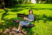 Young Woman Reading Book On The Bench Smiling And Happy. Pretty Young Woman Enjoying Spring In The P