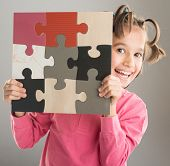 Portrait of funny cute little boy with jigsaw puzzle