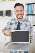 Happy casual businessman pointing to laptop in his office