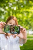 Pretty redhead taking a selfie on her phone in the park on a sunny day