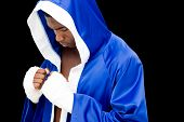 Muscular boxer in in blue hood standing over black background