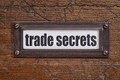 trade secrets text - file cabinet label, bronze holder against grunge and scratched wood