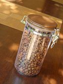 Coffee Beans In Glass Container On Wooden Table.