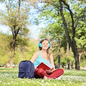 Female student studying on campus seated in a meadow full of flowers shot with tilt and shift lens