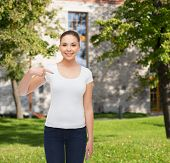 gesture, advertising, summer vacation, education and people concept - smiling young woman in blank w