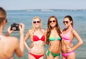 summer vacation, gesture, travel and people concept - group of smiling young women photographing by