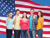 friendship, patriotism and people concept - group of smiling teenagers standing over american flag b