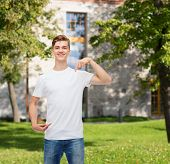 gesture, advertising, summer vacation, education and people concept - smiling young man in blank white t-shirt pointing fingers on himself over campus background