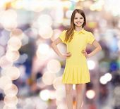 happiness, childhood and people concept - smiling little girl in yellow dress
