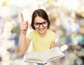 education and school concept - smiling little student girl in eyeglasses with book and finger up